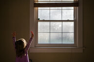 Girl with arms raised standing by window at home - CAVF53289