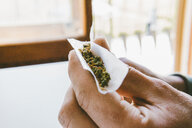 Cropped hand of man rolling marijuana joints in paper at home - CAVF53325