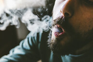 Midsection of bearded man exhaling smoke while smoking marijuana joint at home - CAVF53331