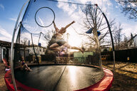 Girl with plastic hoop jumping while sister sitting in trampoline at backyard - CAVF53337