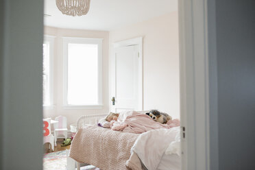 Girl with stuffed toy sleeping on bed at home seen through doorway - CAVF53340