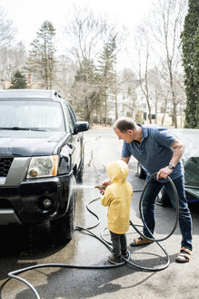 Grandson with grandfather cleaning sports utility vehicle at yard against sky - CAVF53367