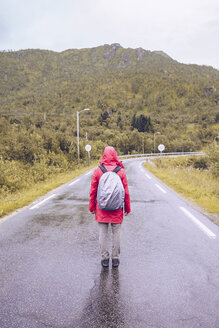 Norway, Lofoten, back view of man wearing red rain acket and backpack standing on wet road - RSGF00051