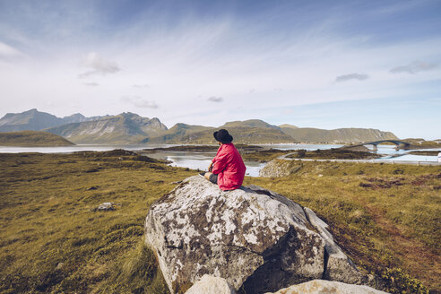 Norway, Lofoten, man wearing red rainjacket sitting on a rock looking at view - RSGF00054