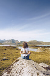 Norway, Lofoten, back view of young woman sitting on a rock doing yoga exercise - RSGF00057