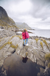 Norway, Lofoten, two women wearing rainjackets standing back to back on a rock - RSGF00066