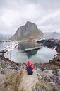 Norway, Lofoten, Hamnoy, back view of man wearing red rainjacket and backpack looking at view - RSGF00069