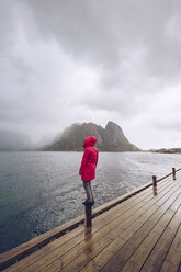 Norway, Lofoten, Hamnoy, man wearing red rain jacket standing on wooden stake looking at distance - RSGF00072