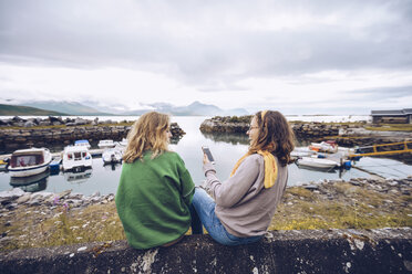 Norway, Senja, two young woman sitting at a small harbor with cell phone - RSGF00075