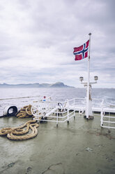 Norway, Senja, Norwegian flag on a ship on the sea - RSGF00084