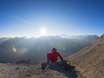 Border region Italy Switzerland, senior man having a break from hiking in mountain landscape at Piz Umbrail - LAF02144