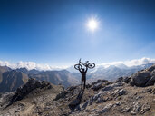 Border region Italy Switzerland, cheering man with mountainbike on peak of Piz Umbrail - LAF02153