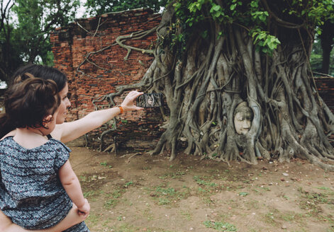 Thailand, Ayutthaya, Mother and daughter taking a photo of the Buddha head in between tree roots at Wat Mahathat - GEMF02465