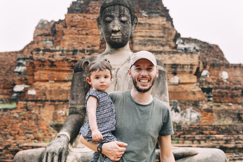 Thailand, Ayutthaya, Portrait of smiling father and daughter at a Buddha statue at Wat Mahathat - GEMF02474