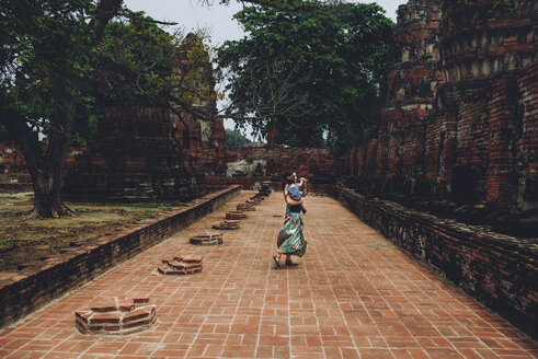 Thailand, Ayutthaya, Mother and daughter dancing in the ancient ruins of a temple at Wat Mahathat - GEMF02477