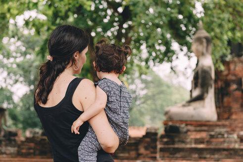 Thailand, Ayutthaya, Mother and daughter looking at a Buddha statue at Wat Mahathat - GEMF02480