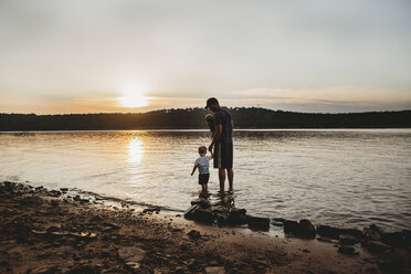 Father with sons standing in lake against cloudy sky during sunset - CAVF53373