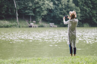 Rear view of woman photographing with mobile phone while standing at lakeshore in forest - CAVF53400
