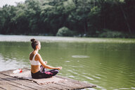 Side view of woman meditating while sitting on pier over lake in forest - CAVF53403