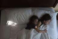 High angle view of sisters sleeping on bed at home - CAVF53412