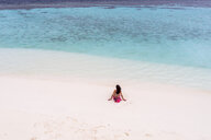 Rear view of woman sitting at sandy beach - CAVF53439