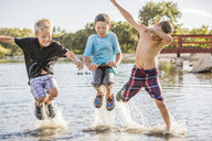 Happy friends jumping in lake - CAVF53451