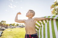 Low angle view of shirtless boy with towel flexing muscles while standing against sky at park - CAVF53454