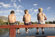Rear view of shirtless friends fishing in lake while sitting on railing against sky - CAVF53463