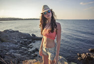 Portrait of confident young woman wearing sunglasses and hat while standing on rocky beach during sunset - CAVF53487