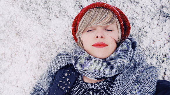 Young woman lying down over a snowy floor - INGF06330