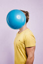 Mid section of man with balloon against his face - INGF06375