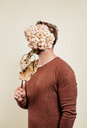 Midsection of man holding a flower bucket against his face - INGF06378