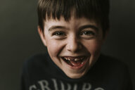 Close-up portrait of happy boy standing against wall - CAVF53516