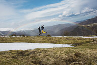 Excited friends jumping against mountains and rainbow during winter - CAVF53519