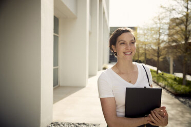Smiling woman holding laptop computer while standing by building in city - CAVF53522
