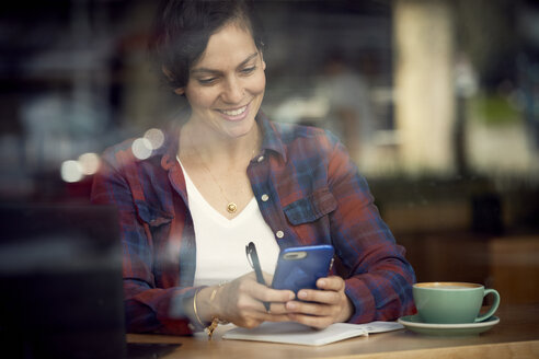 Smiling woman with coffee and book on table using mobile phone in cafe seen through window - CAVF53531