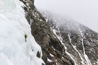 Mid distance view of backpacker ice climbing at White Mountains during winter - CAVF53540