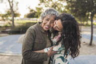 Happy daughter embracing senior mother at park - CAVF53549