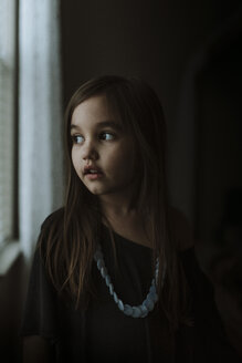 Close-up of thoughtful girl looking through window while standing in darkroom at home - CAVF53567