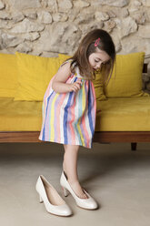 Girl wearing big shoes while standing by sofa at home - CAVF53570