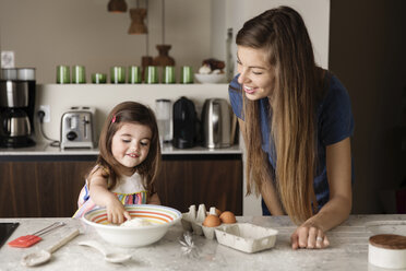 Mother looking at daughter playing with flour on kitchen island - CAVF53573