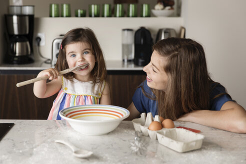 Mother looking at daughter tasting food in kitchen at home - CAVF53576