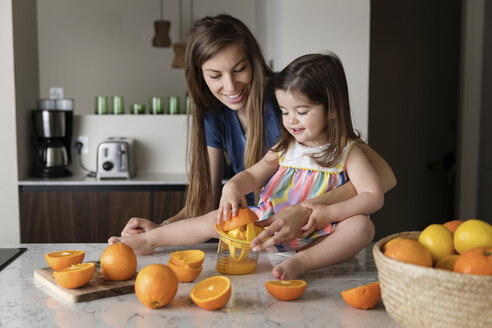 Mother looking at daughter squeezing oranges while sitting on kitchen island - CAVF53579