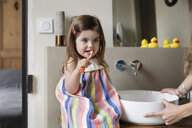 Cropped hands of mother holding sink while daughter brushing teeth in bathroom at home - CAVF53582