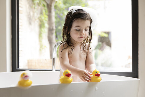 Shirtless girl playing with rubber ducks while bathing in bathtub at home - CAVF53585