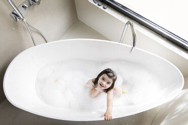 High angle portrait of girl bathing in bathtub at home - CAVF53588