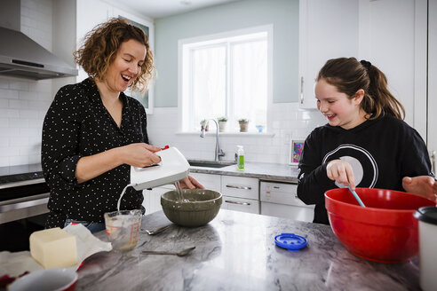 Mother with daughter mixing batter in bowls on kitchen island at home - CAVF53600