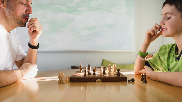 Son playing chess with father on table at home - CAVF53606
