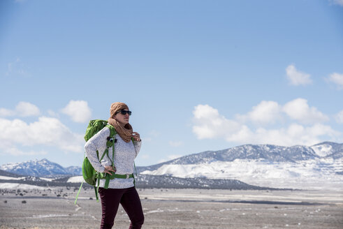 Female hiker with backpack standing at desert against sky during winter - CAVF53621