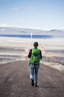 Rear view of hiker with green backpack walking at desert - CAVF53624